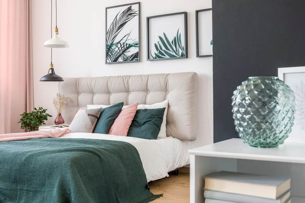 This primary bedroom is decorated with translucent green vase and foliage wall arts mounted above the tufted bed that's lighted by black and white dome pendants.