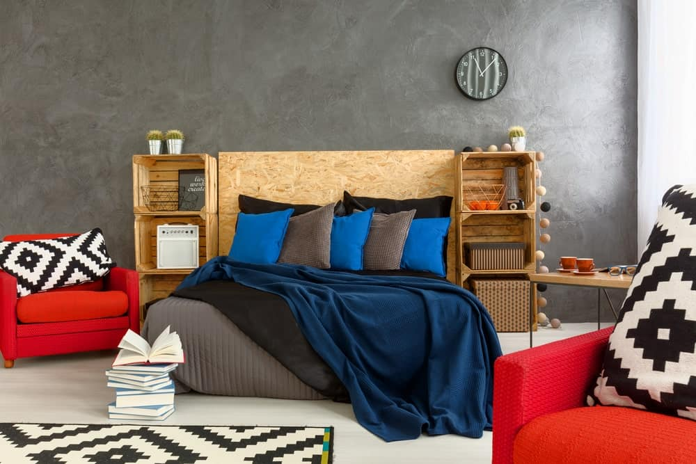 A wooden bed filled with blue and gray pillows complements the shelving units in this primary bedroom with red armchairs and a round wall clock mounted on the concrete wall.