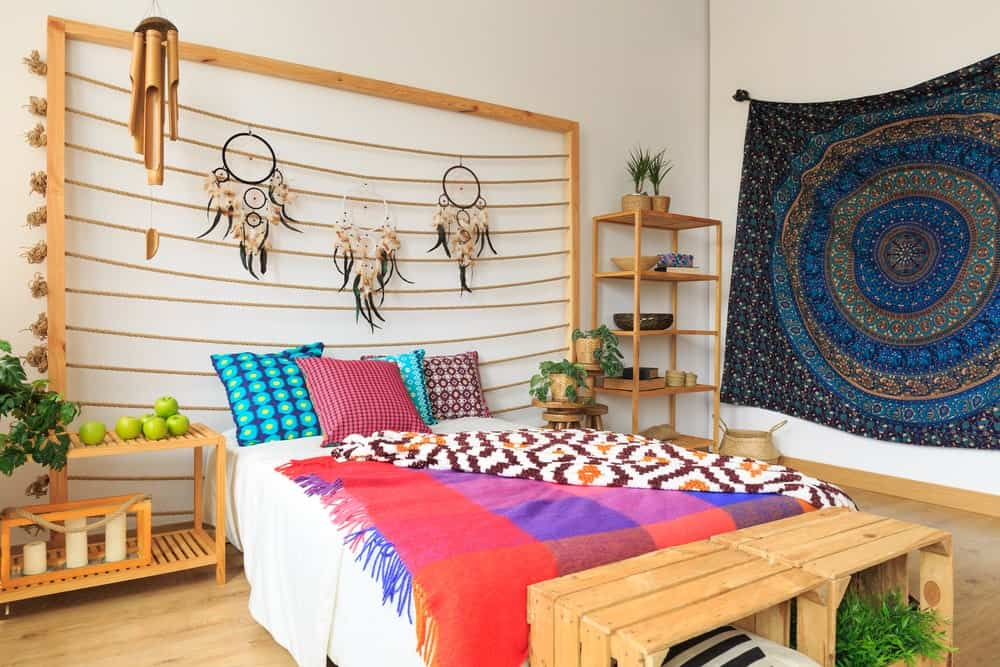 Bohemian style primary bedroom designed with gorgeous tapestry and lovely dream catchers that hung above the white bed accented with multi-colored pillows and throw blankets.