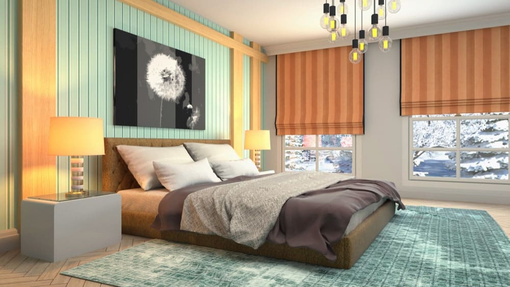 This primary bedroom features a tufted bed on a green patterned rug over herringbone wood flooring. It includes orange striped roman shades and a lovely black artwork mounted on the beadboard wall.