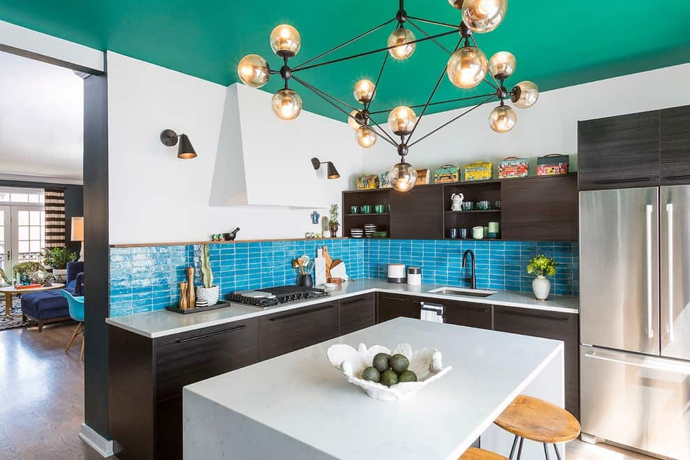 A contemporary chandelier that hung from the green ceiling illuminates the white marble island that's paired with round bar stools. It is contrasted with dark wood cabinets and floating shelves.
