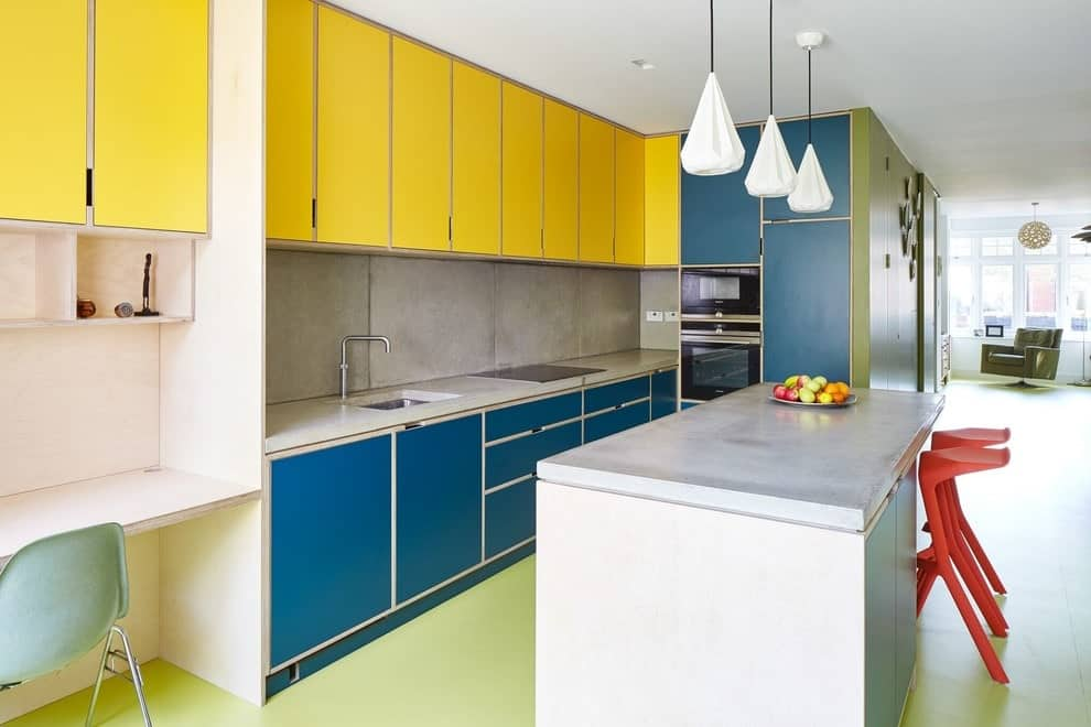 Multi-colored kitchen with blue and yellow cabinetry along with black appliances and concrete tile backsplash that complements the countertops. It includes a white breakfast island with red modern chairs lighted by geometric pendants.
