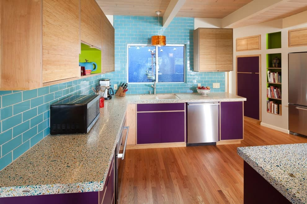 This kitchen showcases purple lower cabinets and light wood upper cabinets fixed against the blue subway tile backsplash. It includes granite countertops and inset shelves filled with books and an antique vase.