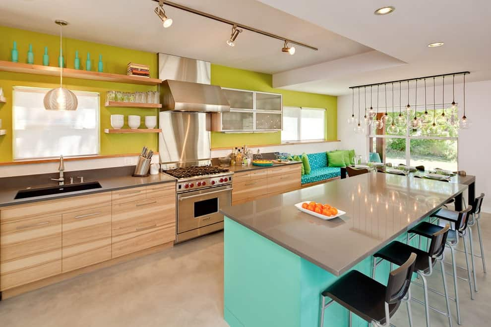Black counter stools sit at an aqua island bar that's topped with a gray counter. It is accompanied by light hood cabinets and a seat nook completed with blue printed cushions and green pillows.