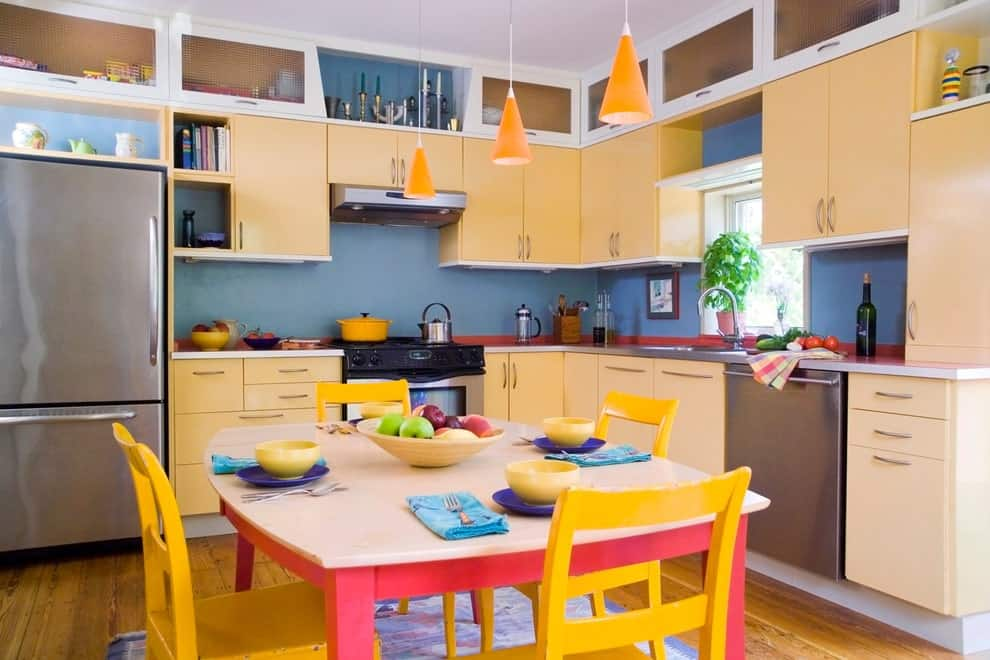 An eat-in kitchen with stainless steel appliances and yellow cabinetry against the blue walls. There's a colorful dining set in the middle lighted by orange cone pendants.
