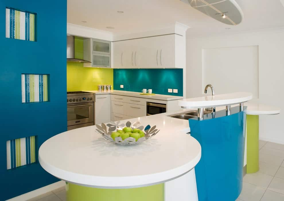 Contemporary kitchen with stainless steel appliances and white cabinetry accented with green and blue backsplash. It includes inset shelves and a modern island topped with a decorative bowl.