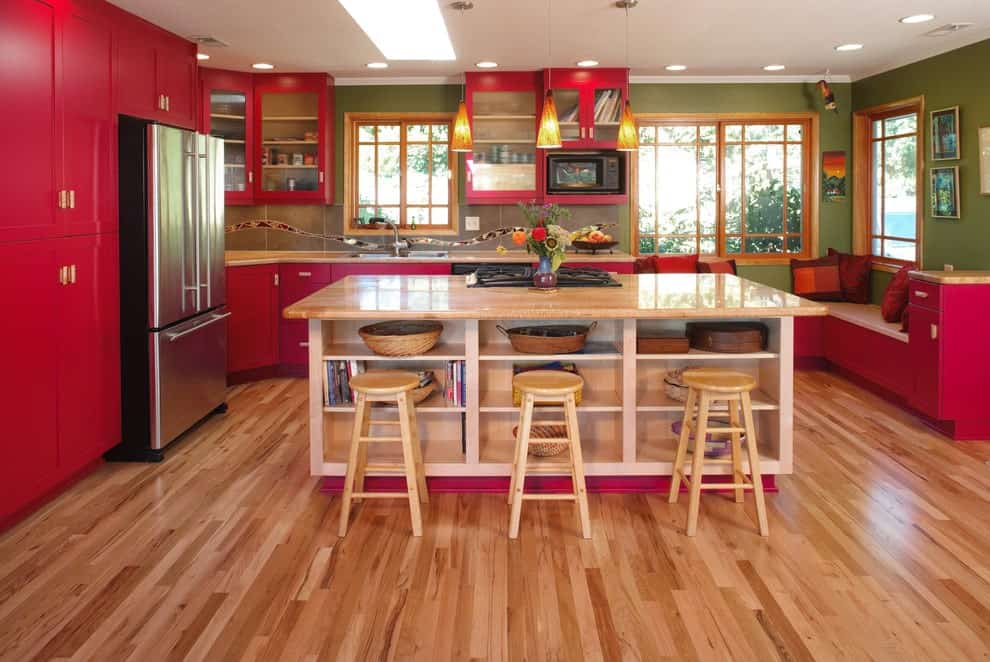 Red cabinetry and a built-in seat add a striking contrast to the green walls that are mounted with lovely artworks. There's a kitchen island in the middle lined with wooden round stools and cone pendant lights.