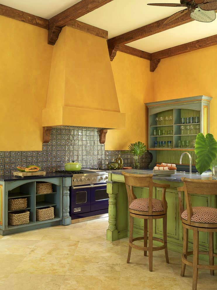 A blue cooking range stands under a yellow vent hood that's fixed on the patterned backsplash tiles. It is accompanied by distressed blue shelves and a green island bar paired with round cushioned stools.