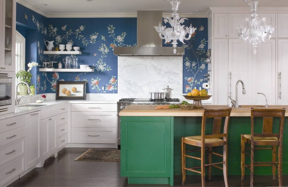 Clad in blue floral wallpaper, this kitchen features white cabinetry and a stainless steel range hood fixed above the marble backsplash. It includes a green island bar with wooden countertop and chairs lighted by gorgeous glass chandeliers.