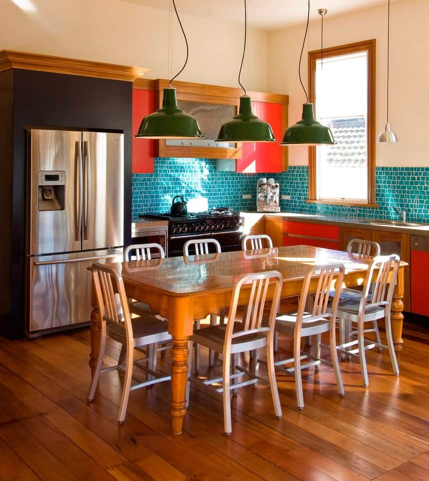 Green dome pendants hang over the wooden dining set blending in with the wide plank flooring. It is accompanied by stainless steel appliances and red cabinets contrasted by blue backsplash tiles.