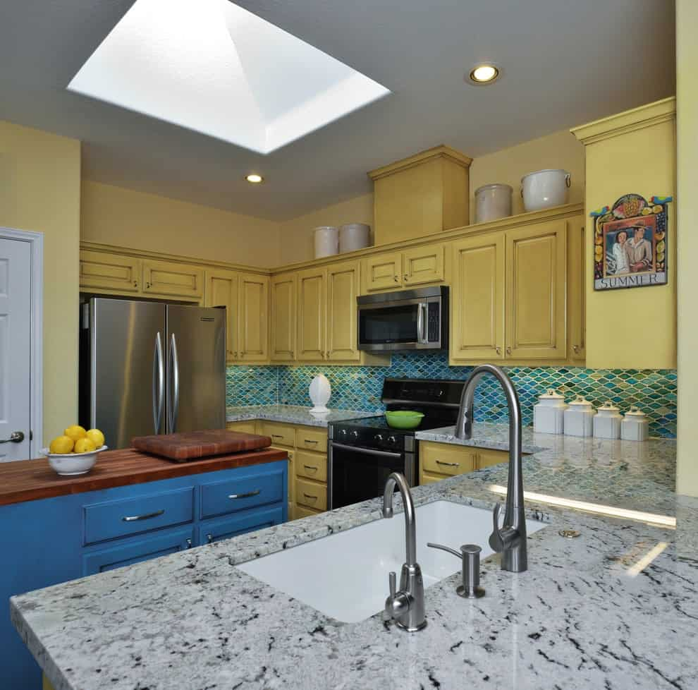 A closeup look at this kitchen with yellow cabinetry and a blue island bar topped with a wooden counter. It is illuminated by recessed lights and a skylight fitted on the gray ceiling.