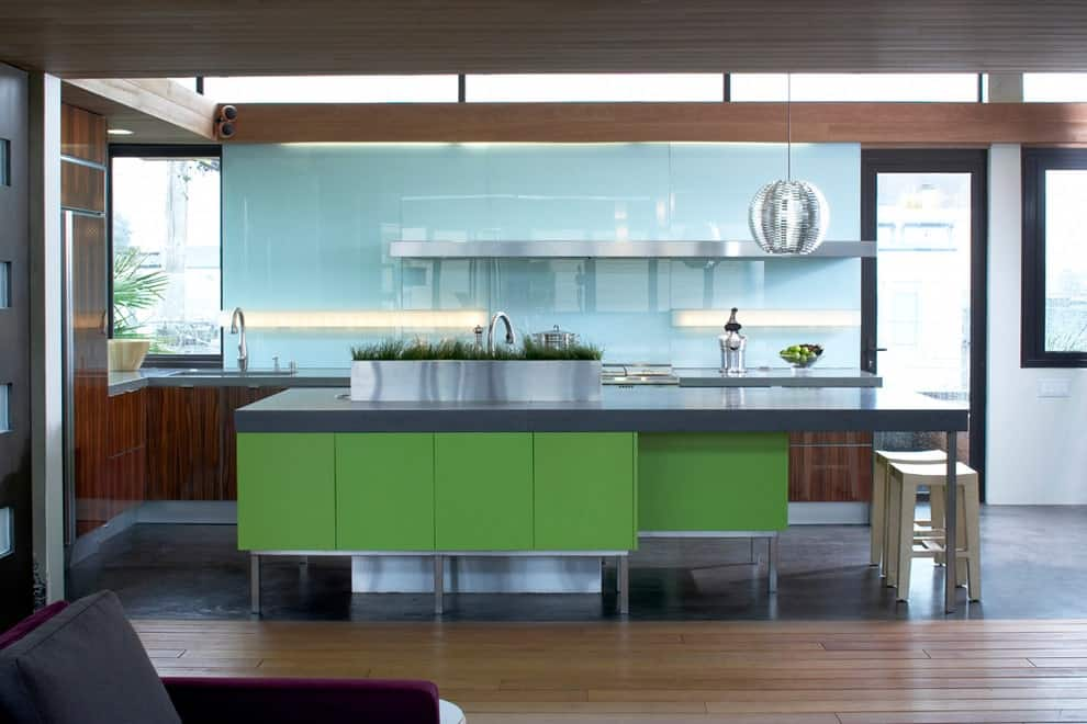 Contemporary kitchen with dark wood cabinets and a green island bar that's topped with a concrete counter. It includes a spherical pendant light and a blue glass backsplash mounted with linear sconces and a floating shelf.