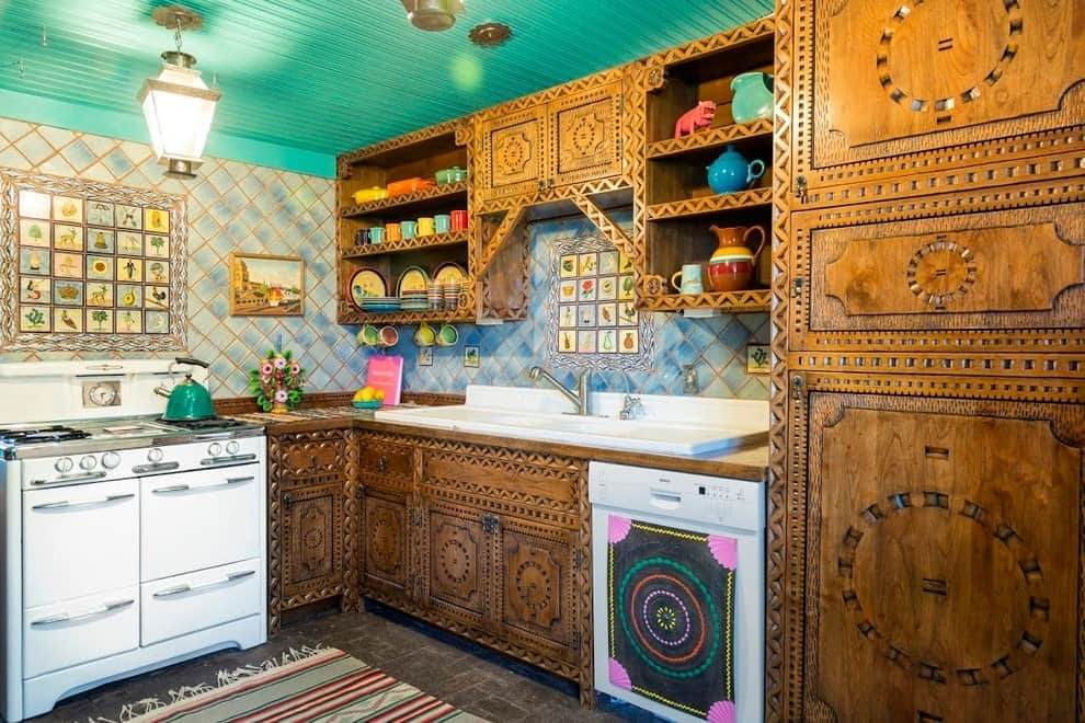 Southwestern kitchen offers white appliances and stylish carved wood cabinets against the blue backsplash tiles. It has a green ceiling and concrete flooring topped by a striped tasseled rug.
