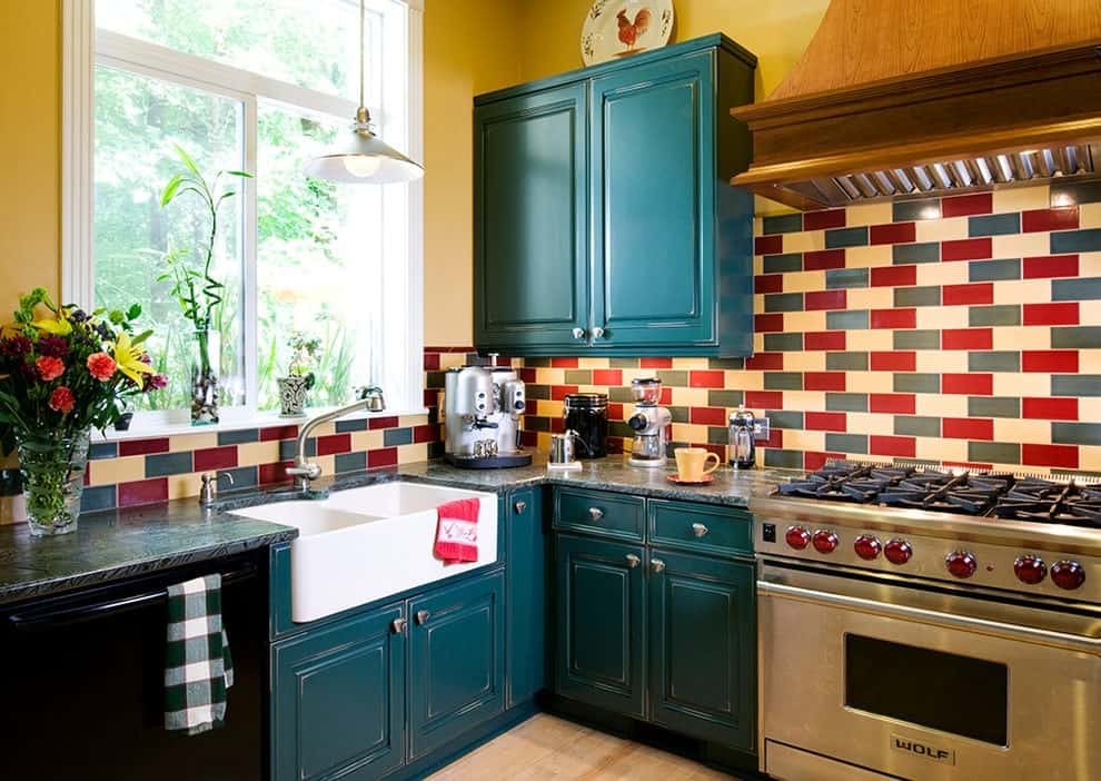 Multi-colored backsplash tiles add a striking accent in this kitchen with blue cabinets and glazed windows allowing natural light in. It has a stainless steel range and a farmhouse dual sink illuminated by a chrome dome pendant.