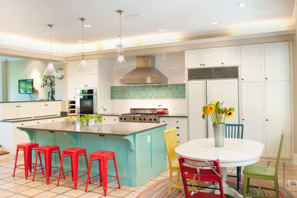 Well-lit eat-in kitchen with white cabinetry and an aqua breakfast bar lined with red stools. It includes glass dome pendants and a white dining table over a round area rug surrounded by multi-colored chairs.