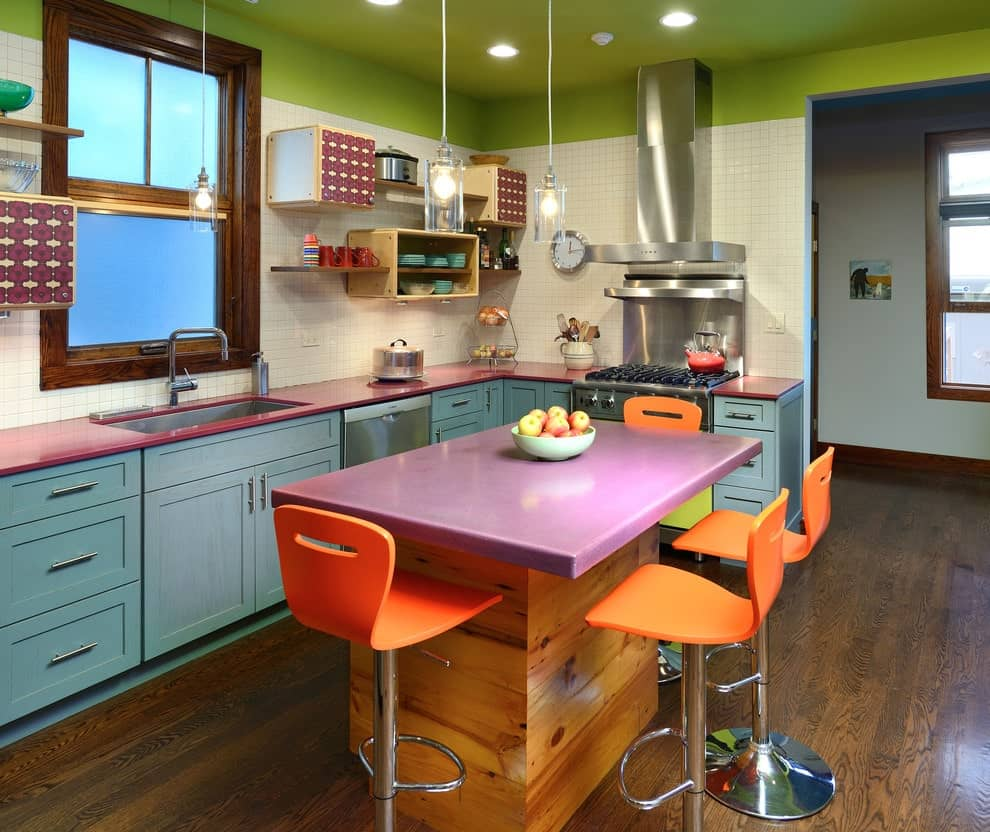Colorful kitchen boasts blue cabinets and a purple top island paired with vibrant orange stools. It has natural hardwood flooring and a green ceiling mounted with recessed lights.