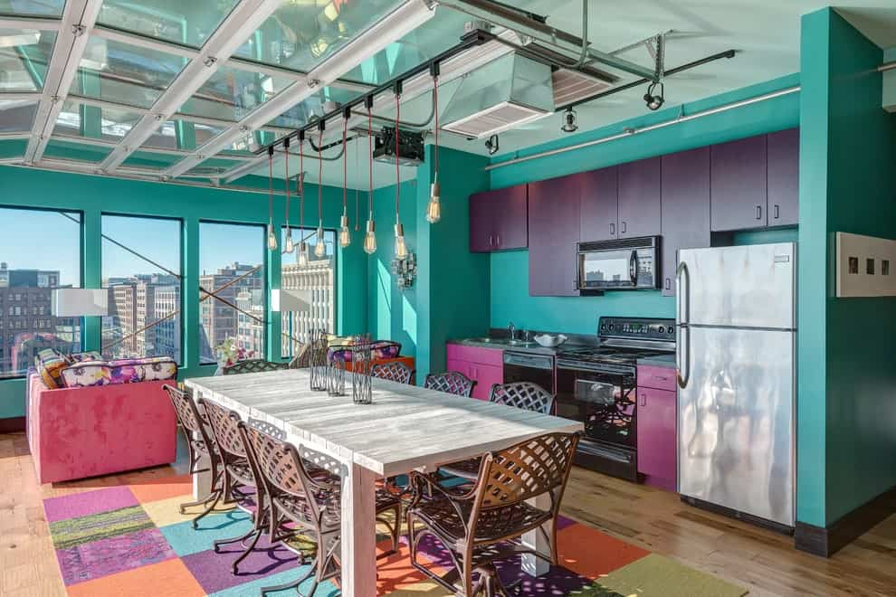 An open concept kitchen boasts bulb pendant lights and a rectangular dining set that sits on a multi-colored rug over the hardwood flooring. It includes stainless steel appliances and purple cabinets fixed against the turquoise wall.