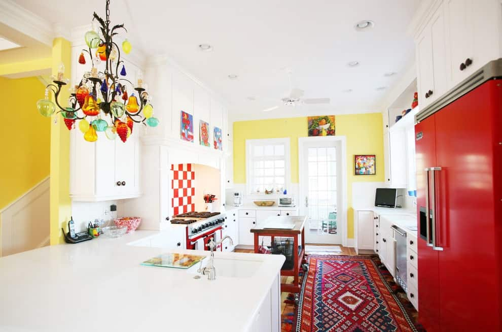 Bright kitchen decorated with lovely artworks and a colorful chandelier that hung over the white peninsula. It has a wooden island and tasseled runner along with a red fridge and cooking range that's accented with a checkered backsplash.