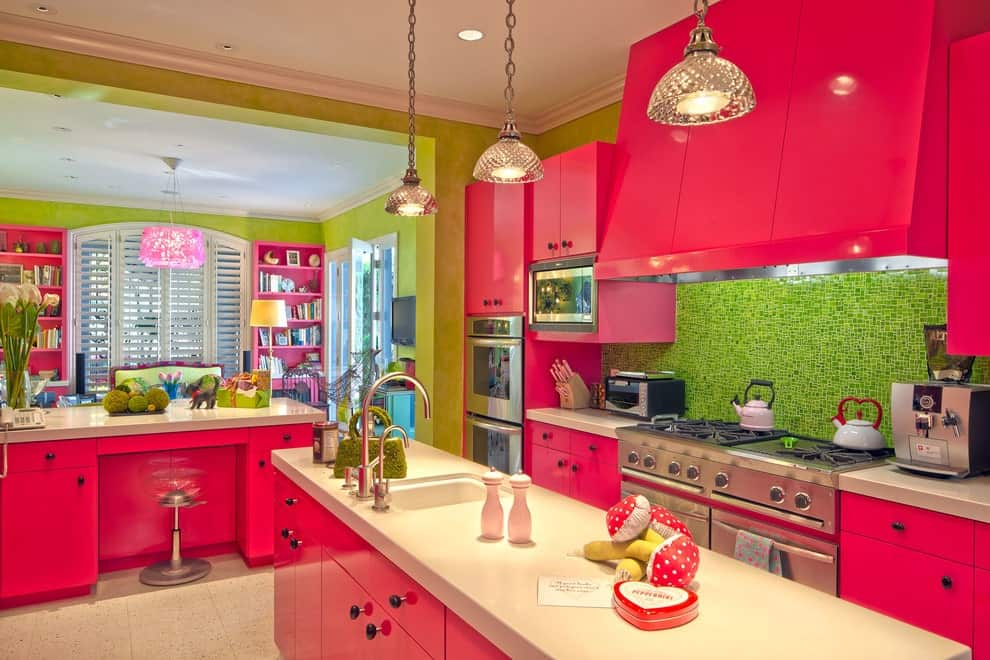 Fuschia pink cabinetry and lime green backsplash and walls create a cheerful tone in this kitchen with crystal dome pendants and a quartz top island bar fitted with a sink and gooseneck faucets.