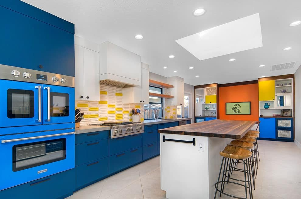 A wooden top kitchen island with a wrought iron towel rack on the side is placed underneath a skylight surrounded with recessed ceiling lights. It is accompanied by metal bar stools along with multi-colored cabinets and appliances.