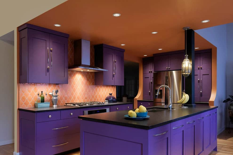 Patterned tile backsplash adds a nice accent to the purple cabinets in this kitchen with stainless steel appliances and a kitchen island that's fitted with a sink and chrome faucet. It has hardwood flooring and an orange ceiling mounted with recessed lights and a vintage pendant.