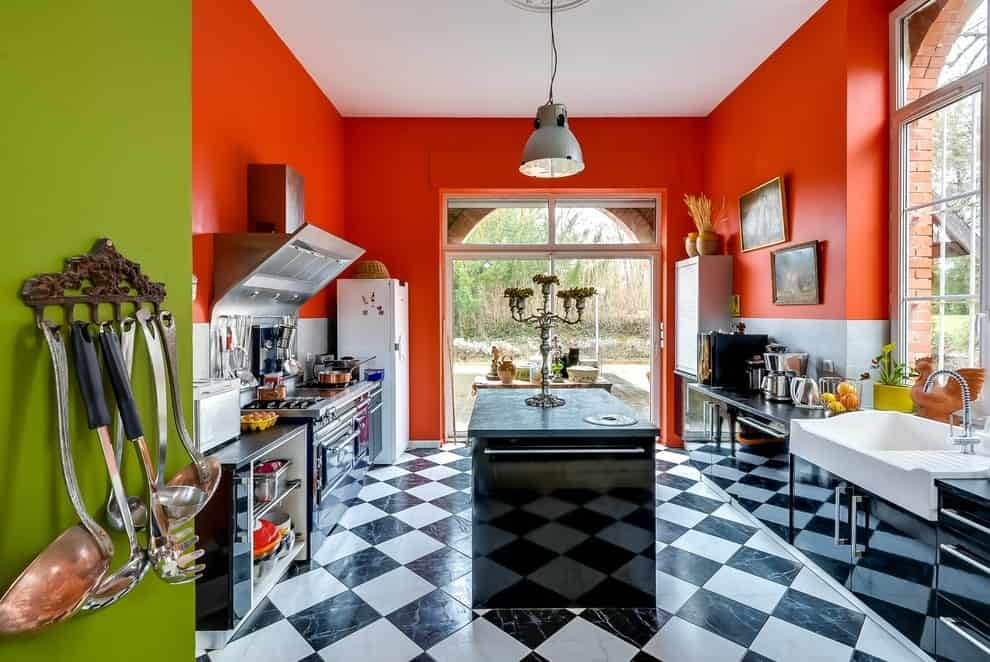 Fresh kitchen with glazed windows and marble tiled flooring arranged in a diamond pattern. It has a white fridge and farmhouse sink contrasted by black cabinets and an island with a high gloss finish.