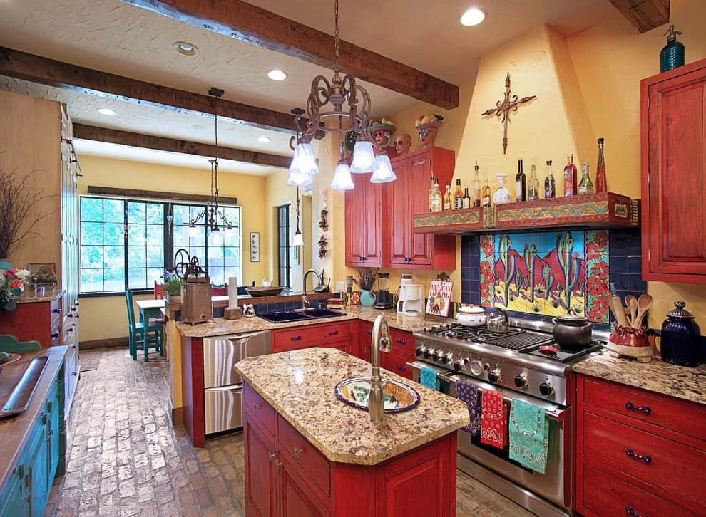 Southwestern kitchen showcases stainless steel appliances along with blue and redwood cabinets matching with the small island that's topped with a granite counter. It includes a vintage chandelier and yellow range hood fixed above a decorative tile mural.
