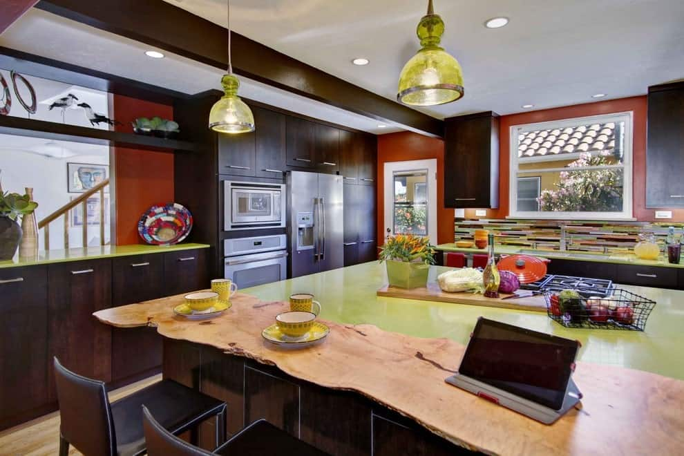 A pair of translucent dome pendants along with recessed ceiling lights illuminate this kitchen offering an immense breakfast island and dark wood cabinetry accented with green countertops and multi-colored backsplash.