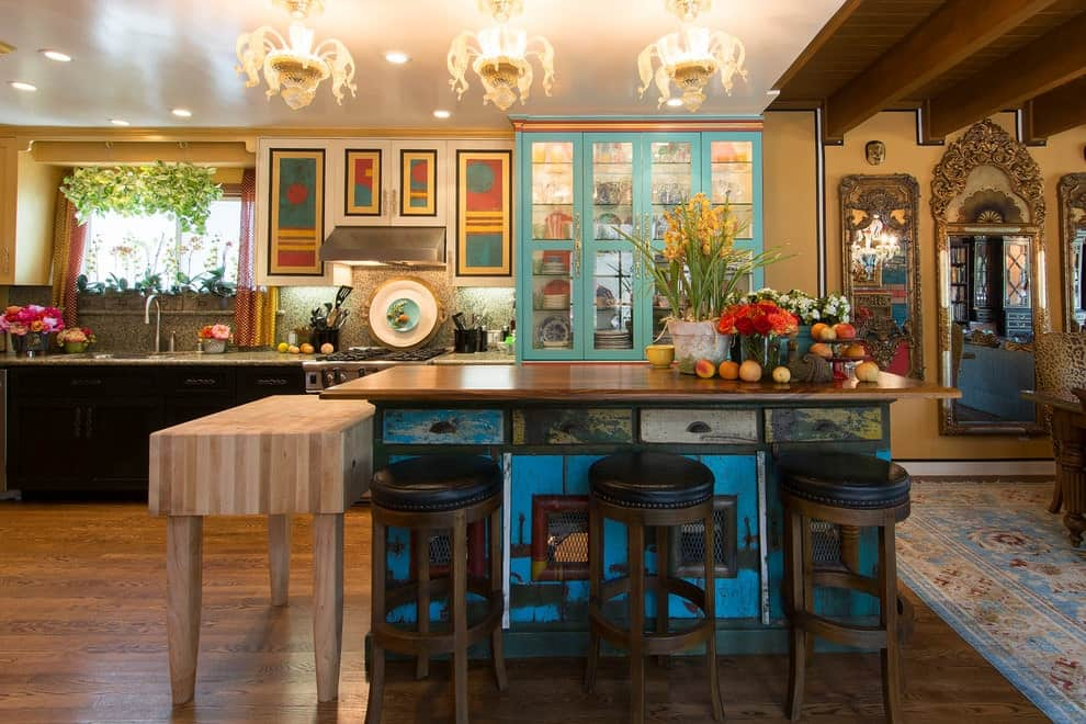 Round cushioned stools sit at a distressed blue kitchen island that's topped with a wooden counter. There's a light wood table on the side illuminated by gorgeous glass chandeliers.