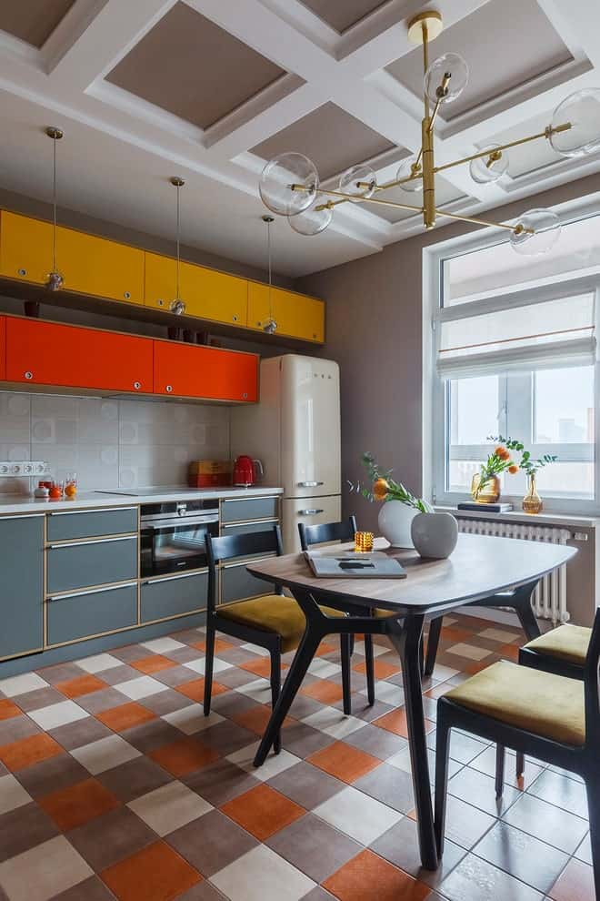 An eat-in kitchen with multi-colored cabinets and cozy dining set lighted by a brass chandelier that hung from the coffered ceiling. It has checkered flooring and white framed windows inviting natural light in.