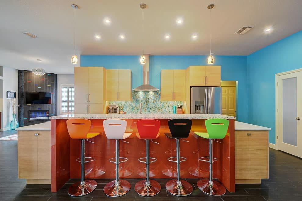 Light wood cabinetry complements the immense breakfast island that's attached with an orange high gloss eating counter. It is lined with glass pendant lights and multi-colored bar stools.