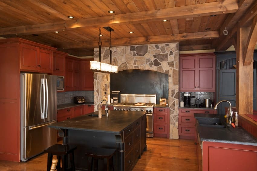 The cozy kitchen offers a stone cooking alcove and red cabinetry with wrought iron hardware. There's a black breakfast island in the middle lighted by a linear pendant that hung from the wood beam ceiling.