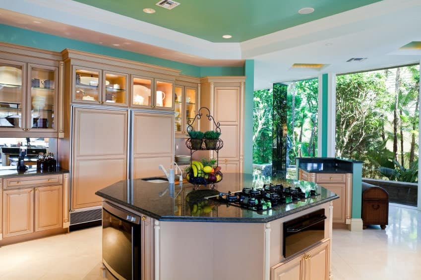 This kitchen features an octagonal island topped with black granite counter and matches the peach cabinetry against the turquoise walls. It has beige tiled flooring and green tray ceiling mounted with recessed lights.