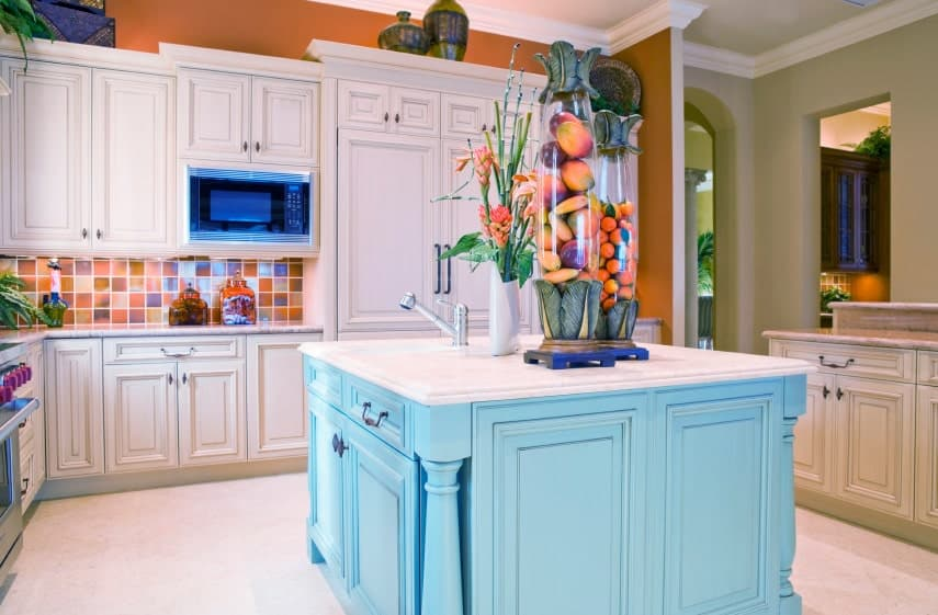 Orange mosaic backsplash tiles add a stunning accent to the white cabinetry in this kitchen with a blue central island that's fitted with a porcelain sink and chrome fixtures.