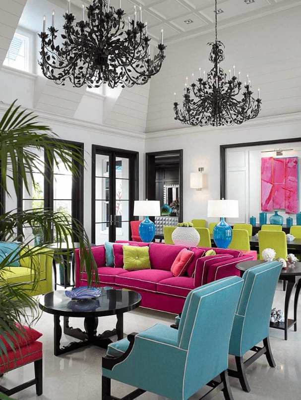 A pair of black chandeliers illuminate this living room offering colorful seats and a round coffee table topped with a decorative bowl. It has tiled flooring and a palm plant on the side creating a tropical feel in the room.