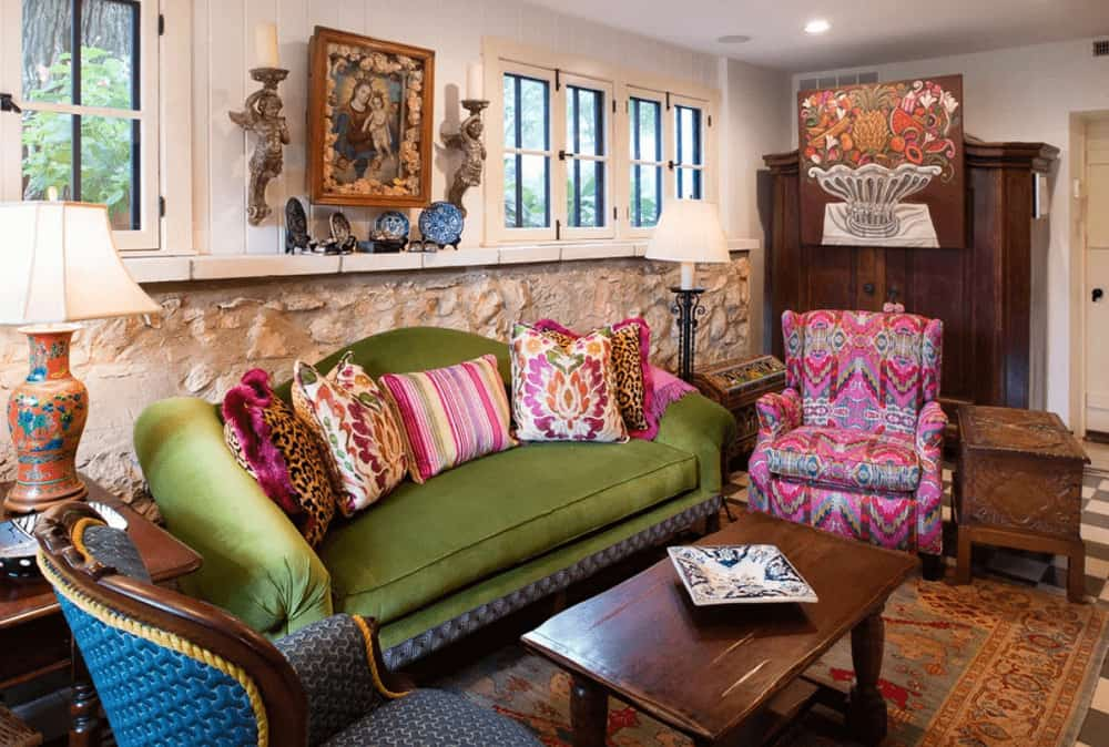 A pink printed chair complements the various styled pillows on a green sofa against the textured wall. It is accompanied by a blue patterned chair and a wooden coffee table over a vintage area rug.