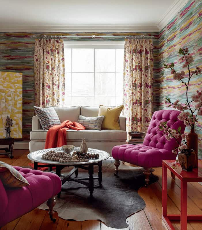 Clad in colorful wallpaper, this living room offers a beige sofa and pink tufted chairs flanking a round coffee table that sits on a cowhide rug. It has wide plank flooring and white framed windows dressed in printed draperies.
