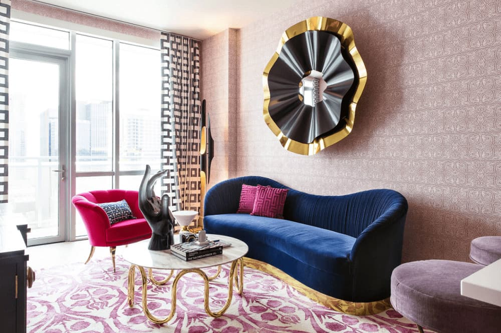 A unique round mirror hangs above the blue velvet sofa paired with a stylish coffee table. It is accompanied by round stools and a pink glam chair against the full height windows dressed in geometric draperies.