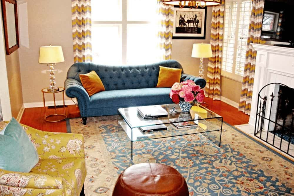 The multi-colored living room features a yellow floral chair and blue tufted sofa paired with a glass top coffee table. It includes a classic printed rug and a white fireplace enclosed in a wrought iron fence.