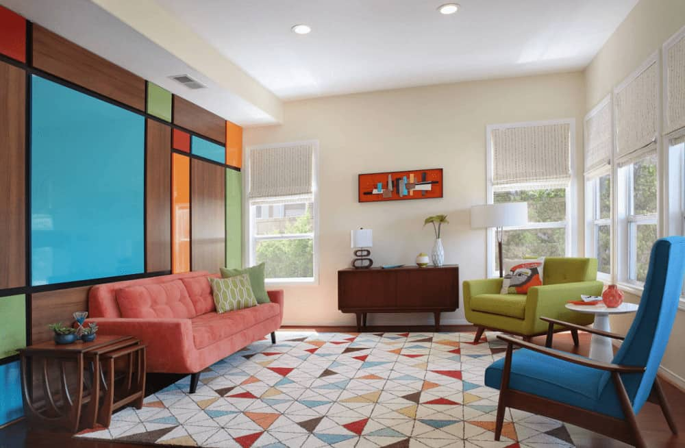 A colorful paneled wall is the highlight in this living room with multi-colored seats and a geometric area rug that lays on the smooth hardwood flooring. It has a rectangular artwork and a wooden console table complementing with the modular side table.