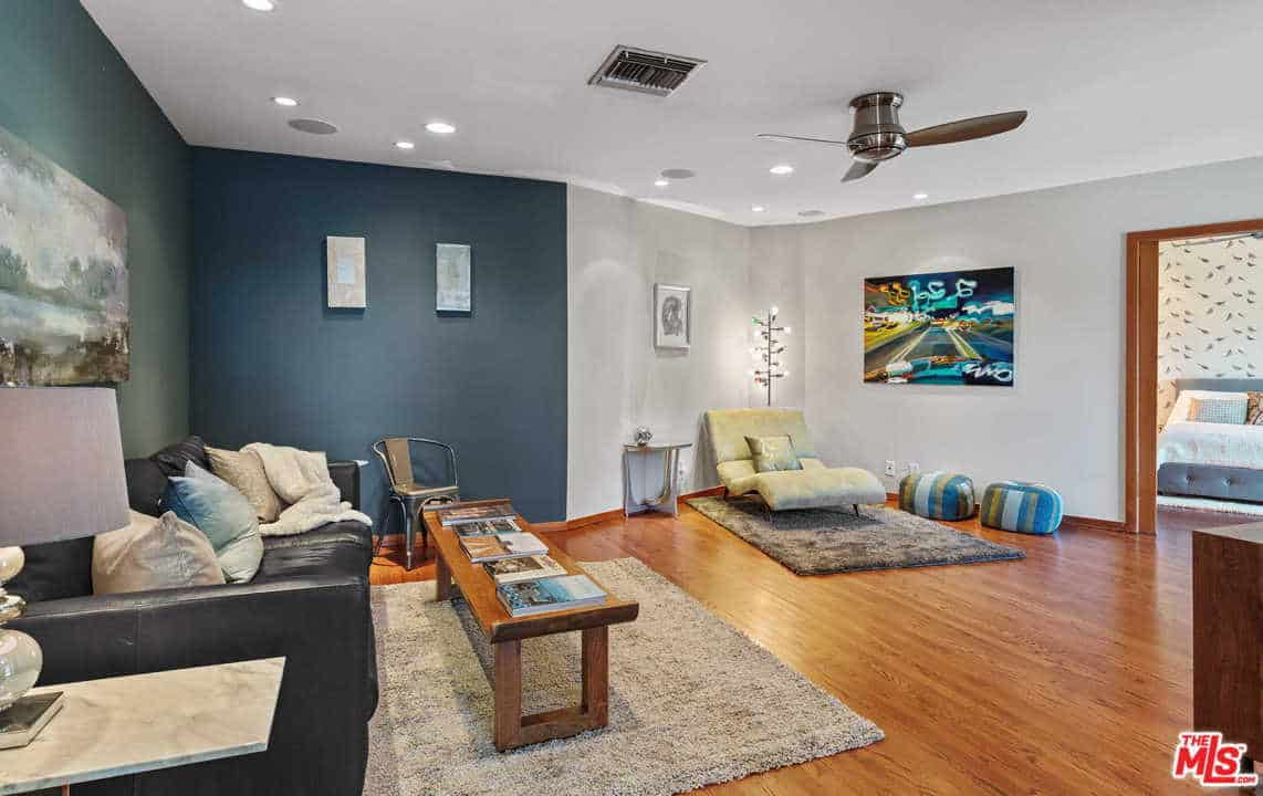 Recessed ceiling lights illuminate this living room along with a multi-head bulb floor lamp that sits behind the velvet lounge chair. It has two-tone walls and a rich hardwood flooring topped by shaggy rugs.