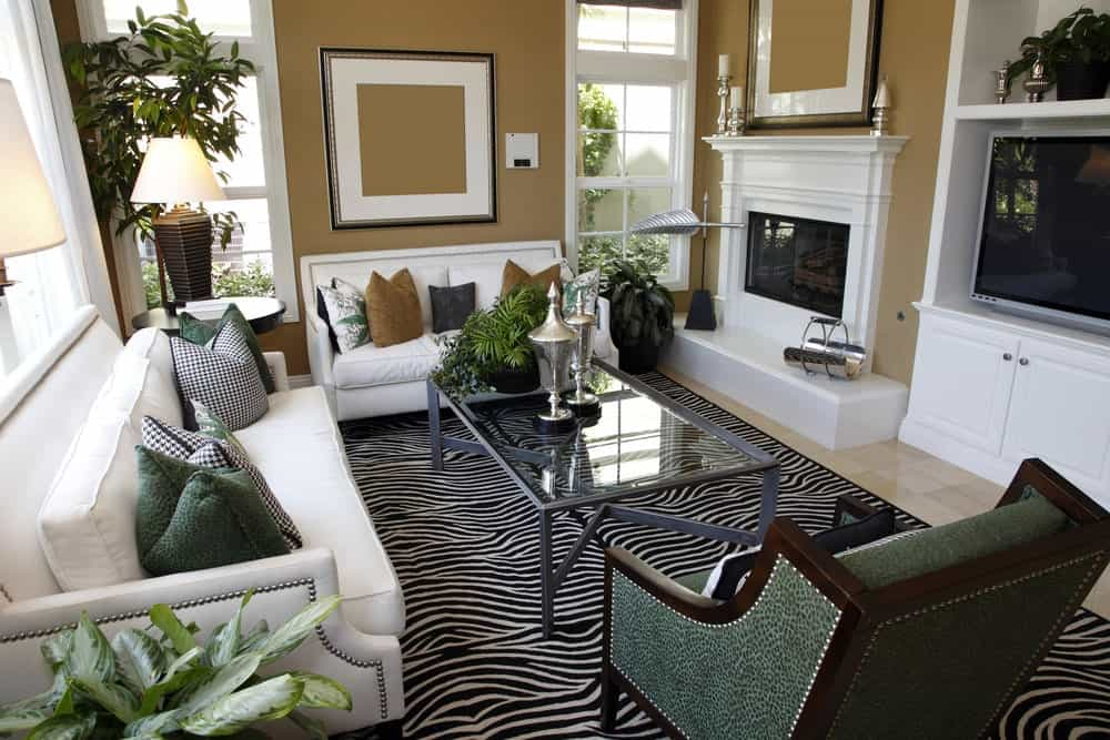 The tropical living room boasts white sofas and a green armchair paired with a glass top coffee table that sits on a zebra rug. It includes a flat-screen TV and a fireplace fixed on the beige wall.