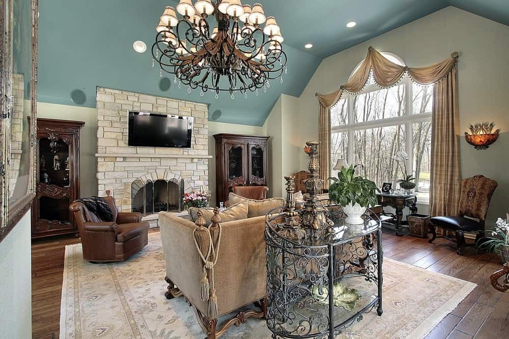 Sophisticated living room illuminated by an ornate chandelier and recessed lights fitted on the blue vaulted ceiling. It has brown seats and a brick fireplace with a wall-mount TV on top.