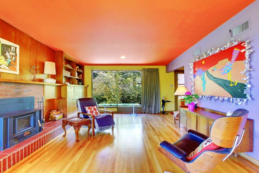 Living room with orange ceiling, multi-colored walls, a brick fireplace, and wood flooring.