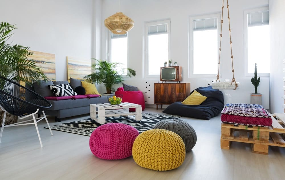 Multi-colored ottoman and seats bring a pop of color in this living room with a vintage TV and white coffee table on a black patterned rug illuminated by a wicker pendant light.