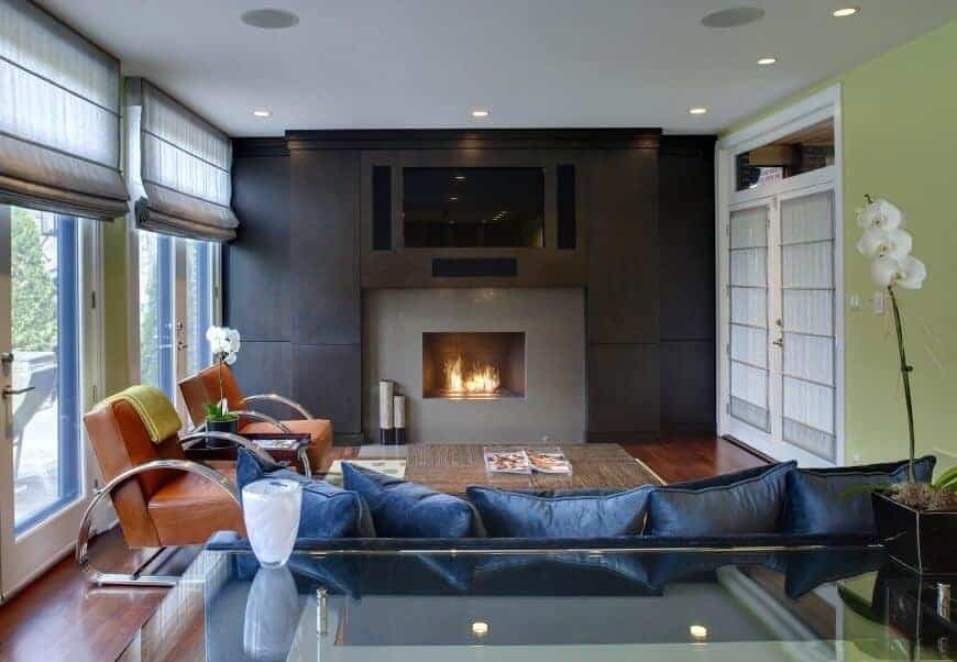 A wall-mount TV hangs above the sleek fireplace facing the sofa that's filled with blue velvet pillows. It is accompanied by leather chairs with chrome arms against the glazed doors that are covered in translucent roman shades.