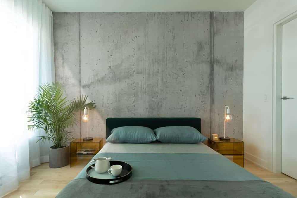 A potted palm plant creates a refreshing ambiance in this industrial-style primary bedroom featuring a platform bed that's placed against the concrete accent wall. It is flanked by translucent nightstands and bulb table lamps.