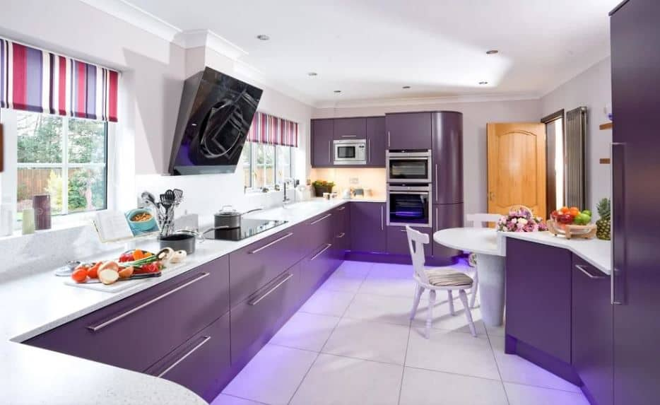 The brightness of this white kitchen is somewhat counterbalanced by the deep purple hues of the wide U-shaped peninsula that has cabinets and drawers with stainless steel handles that pair well with the modern appliances.
