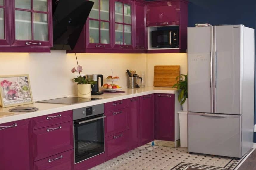 The deep purple floating cabinets has frosted glass panels on its cabinet doors that augments the homey quality of the kitchen. This pairs well with the L-shaped peninsula's cabinets and drawers that houses the oven and the fridge.