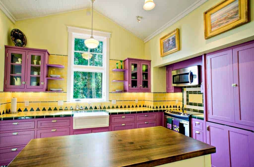 The sunny yellow walls and backsplash tiles of this kitchen is contrasted by an equally cheerful pastel purple hue that can be seen on the cabinets and drawers of the L-shaped peninsula as well as the floating cabinets with glass panels and built-in shelves flanking the window.